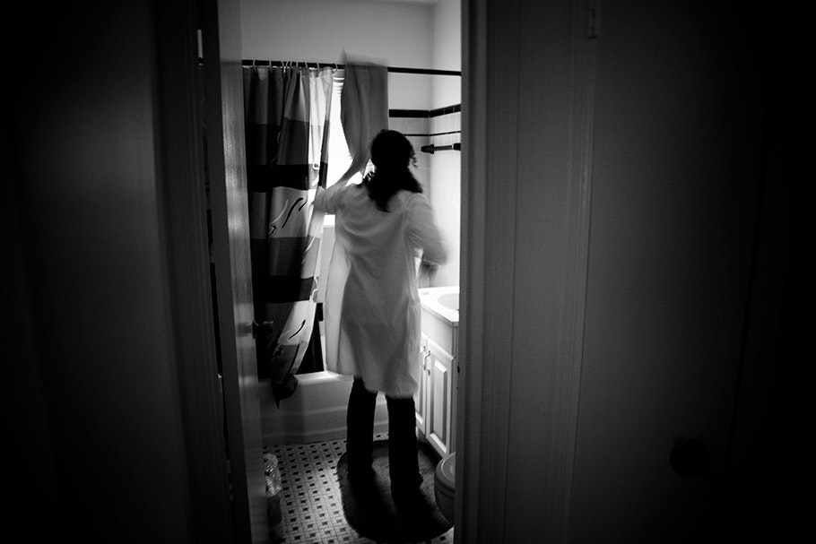 Woman standing in bathroom.