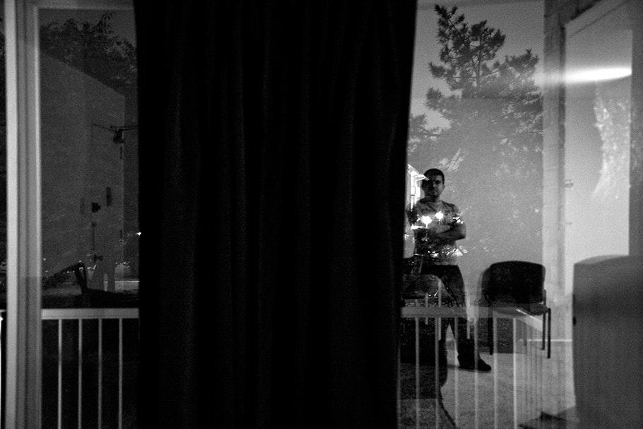 Man seen through window with railing.
