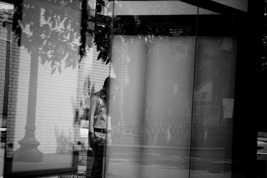 Man in front of brick wall seen through reflection.
