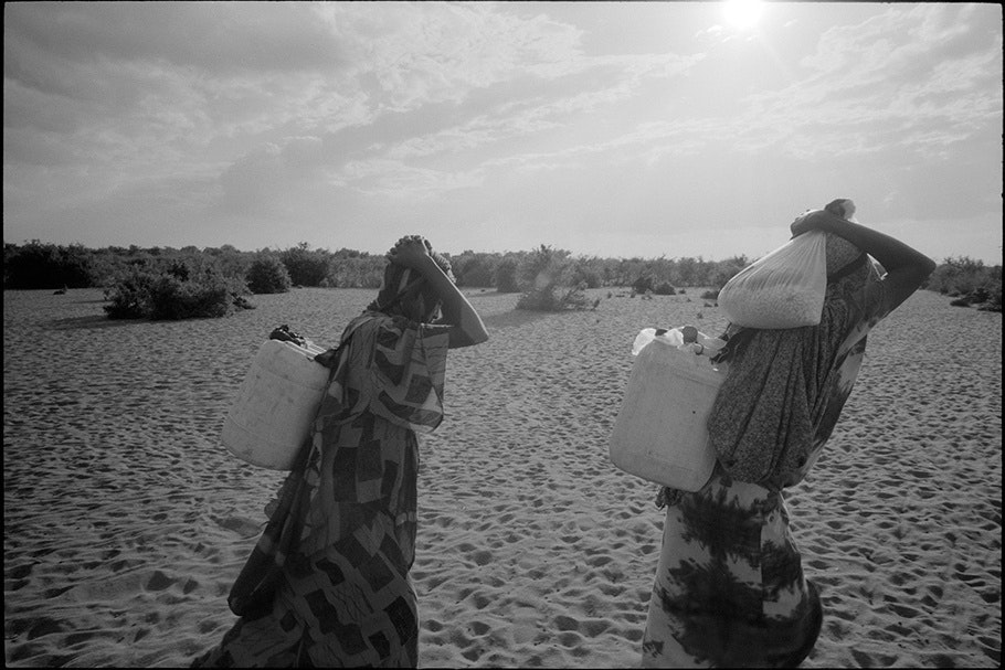 Women carrying supplies on their backs.