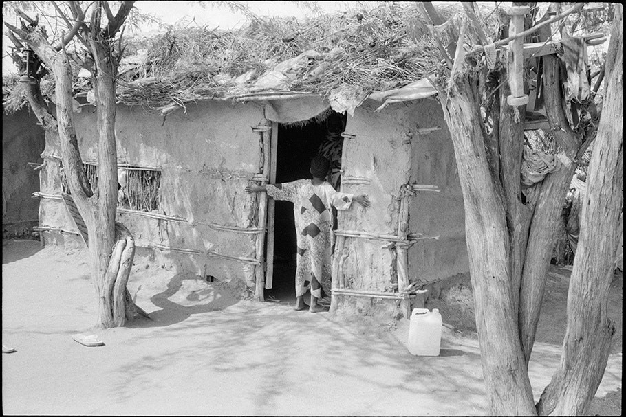 Child facing into the doorway of a house.