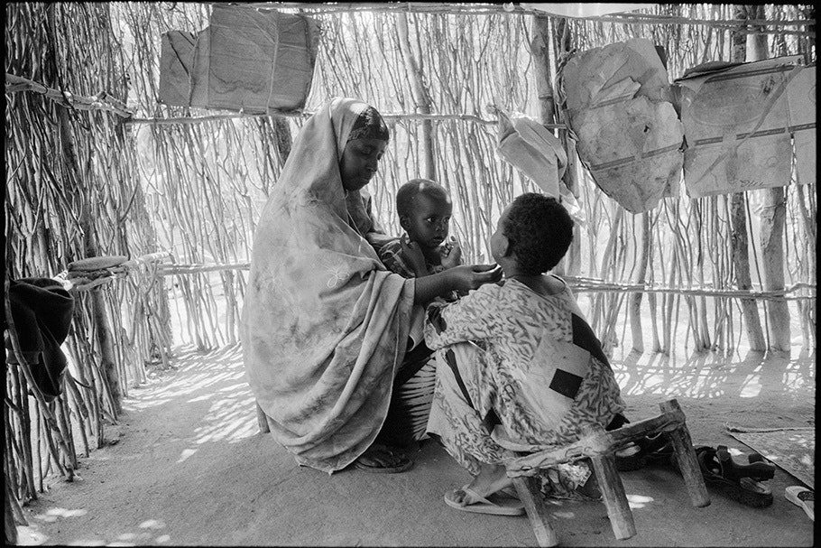 Woman with two children in front of a wall made of sticks.