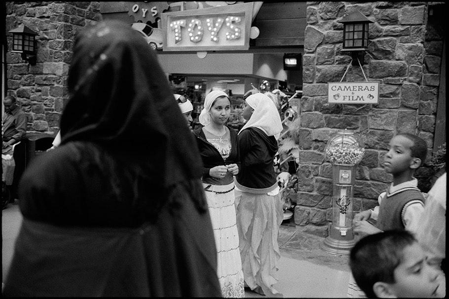 "Women walking under ""toys"" sign."