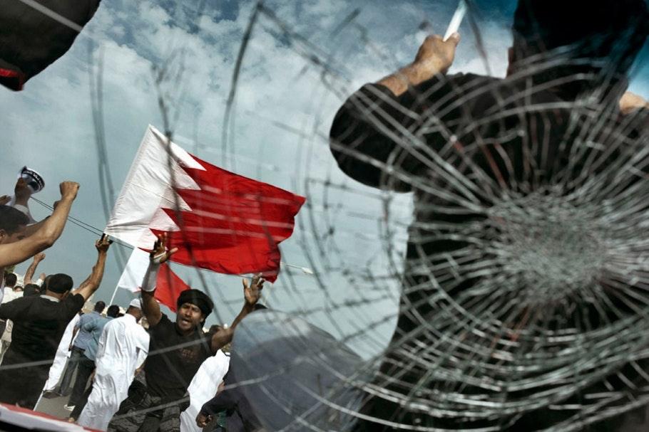 A man holding a flag seen through broken glass.