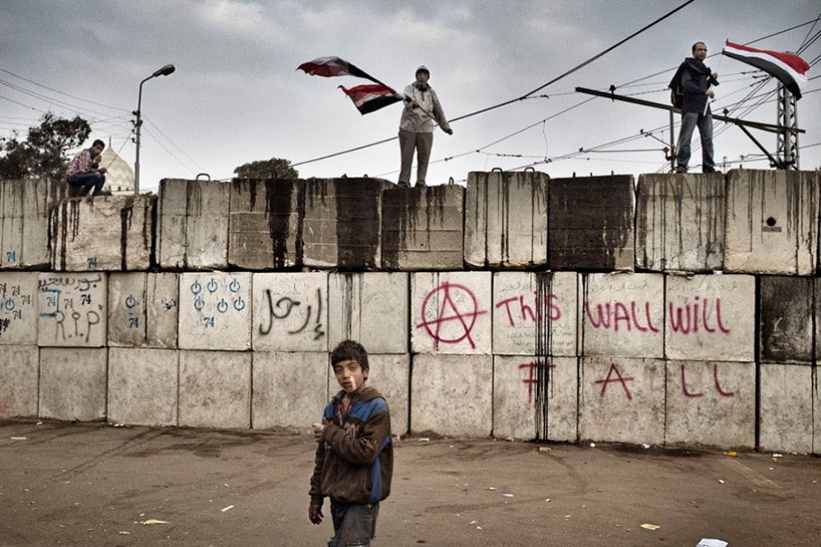 A boy stands in front of a temporary cement wall.