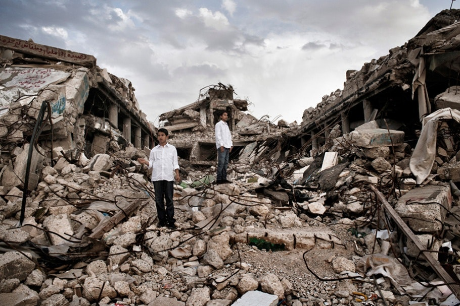 Boys standing on building rubble.