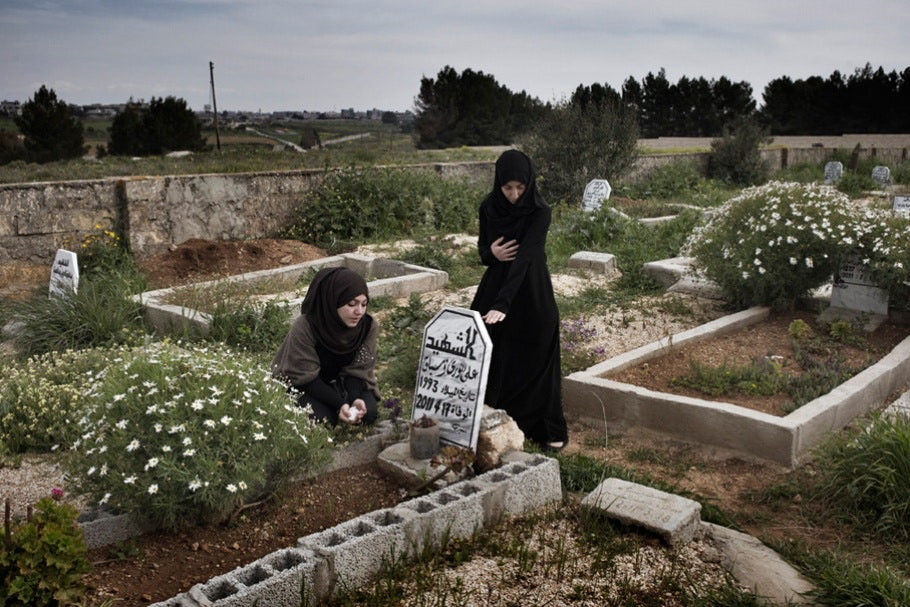 Two women at a grave.