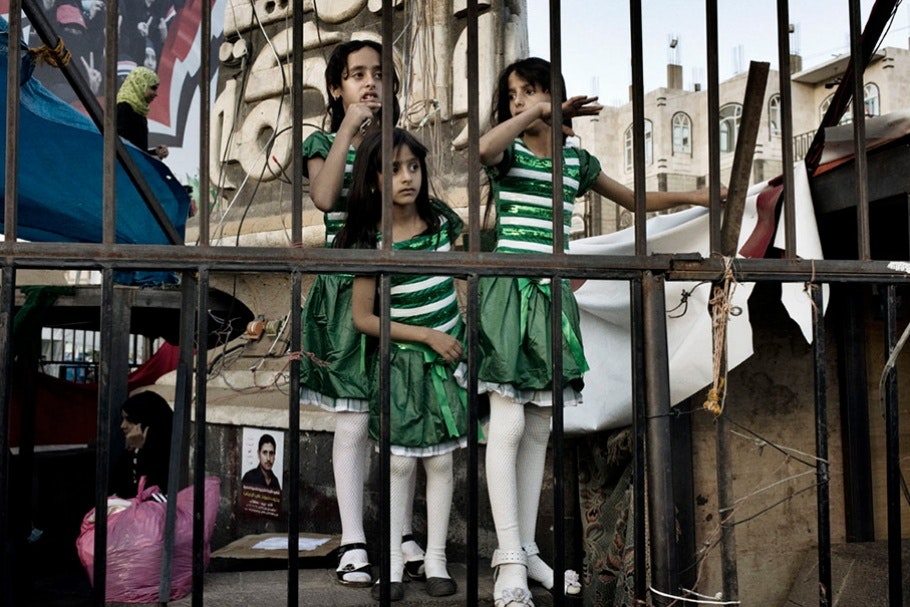 Three little girls stand by a metal fence.