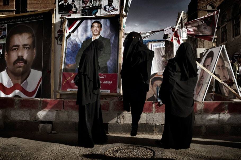 Three women stand on the street dressed in all black.