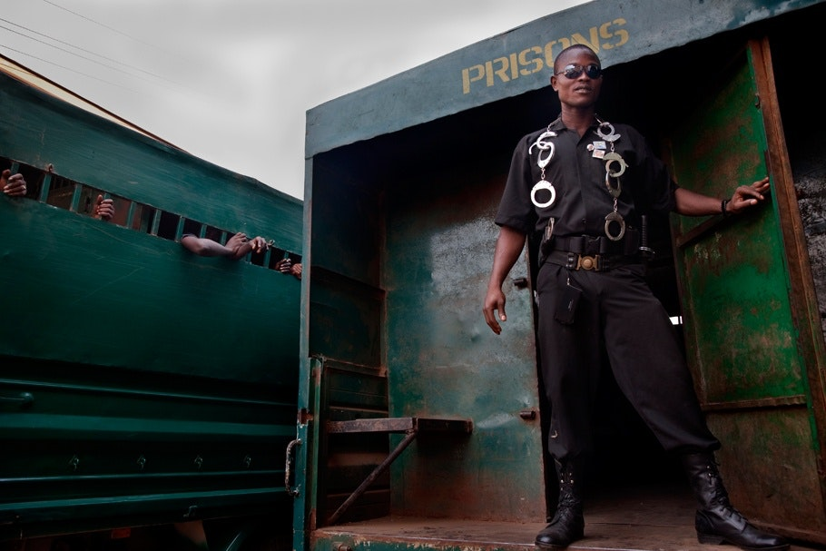 A prison guard stands in front of a door.