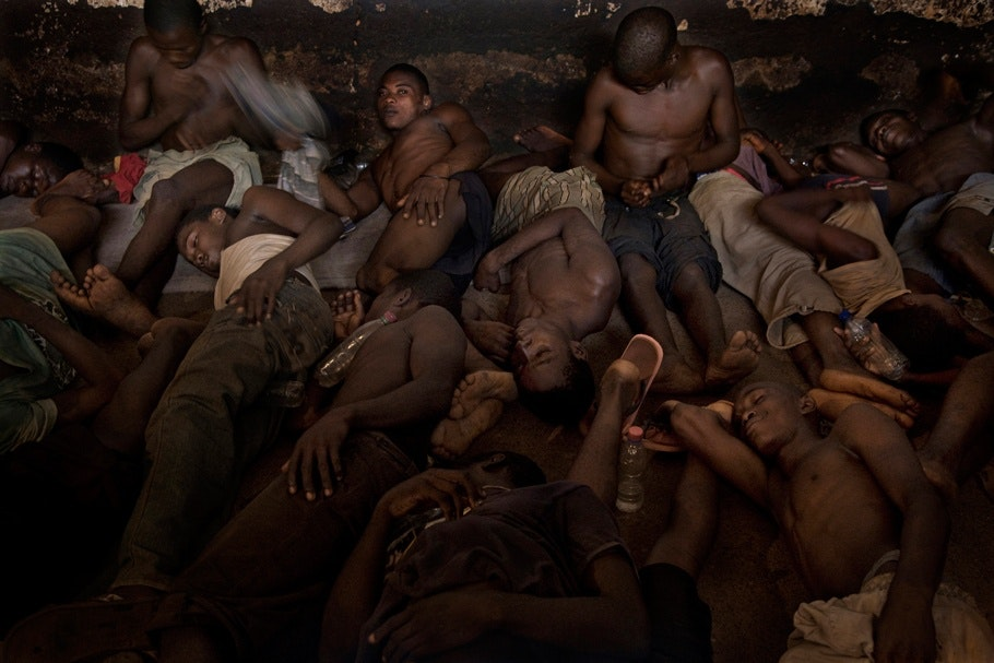 A group of men lying down in a tight space.