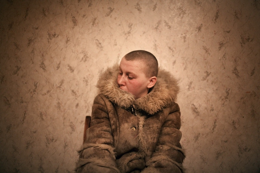 A woman with a shaved head sits in a chair.
