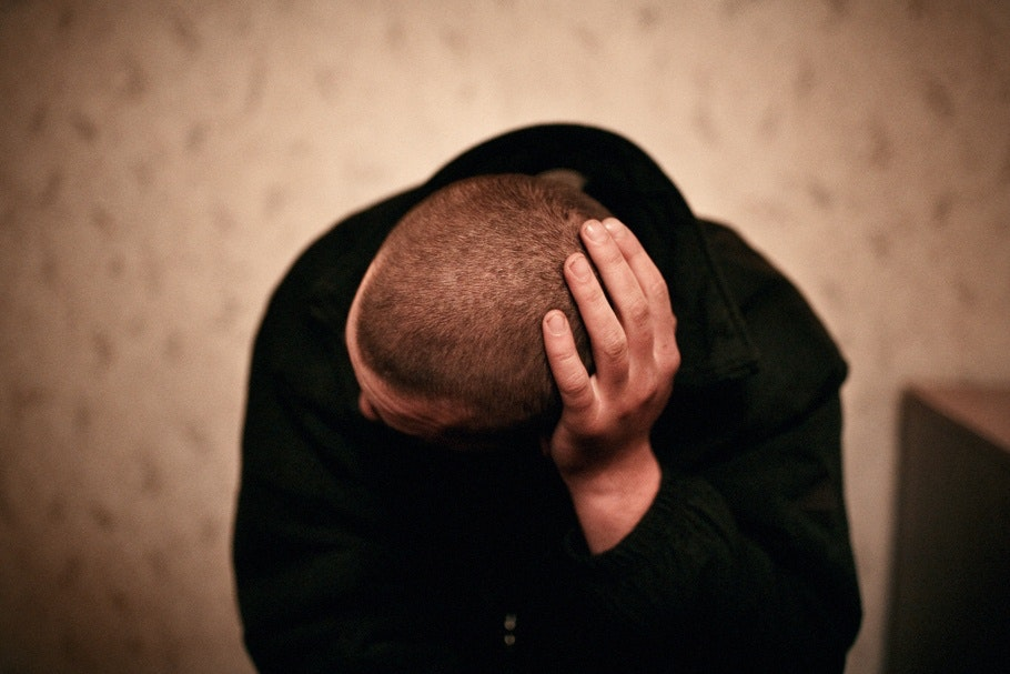 A man rubs his head.