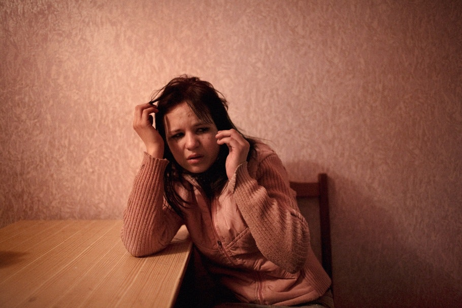 A crying woman leans on a desk.