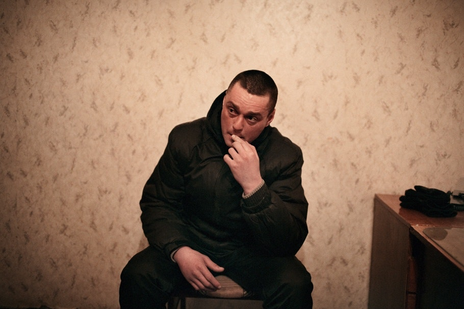 A man sitting bites his finger.