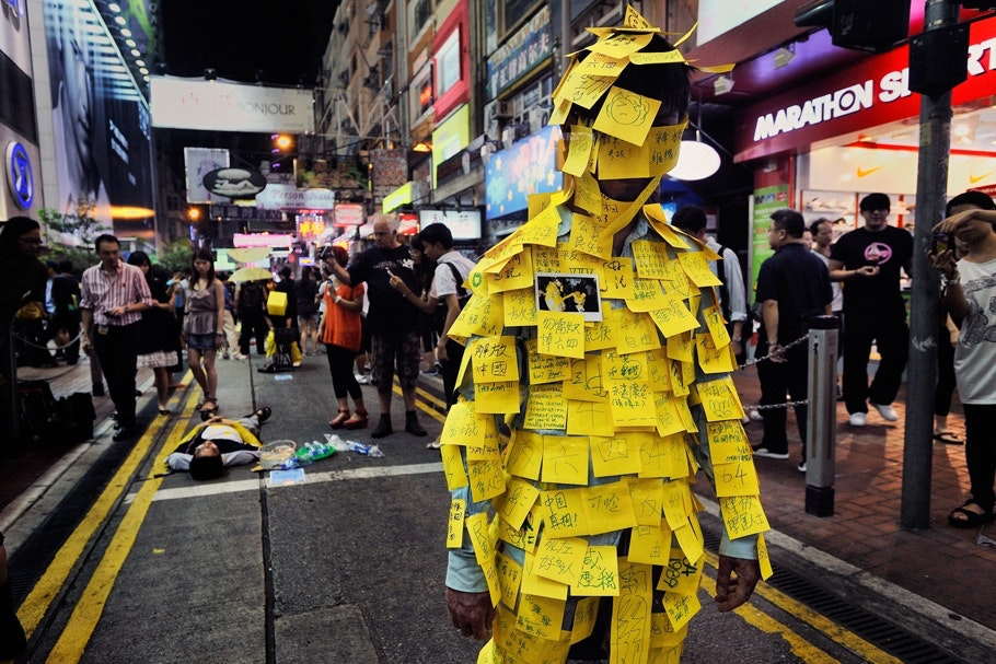 Man standing in street covered in Post-it notes