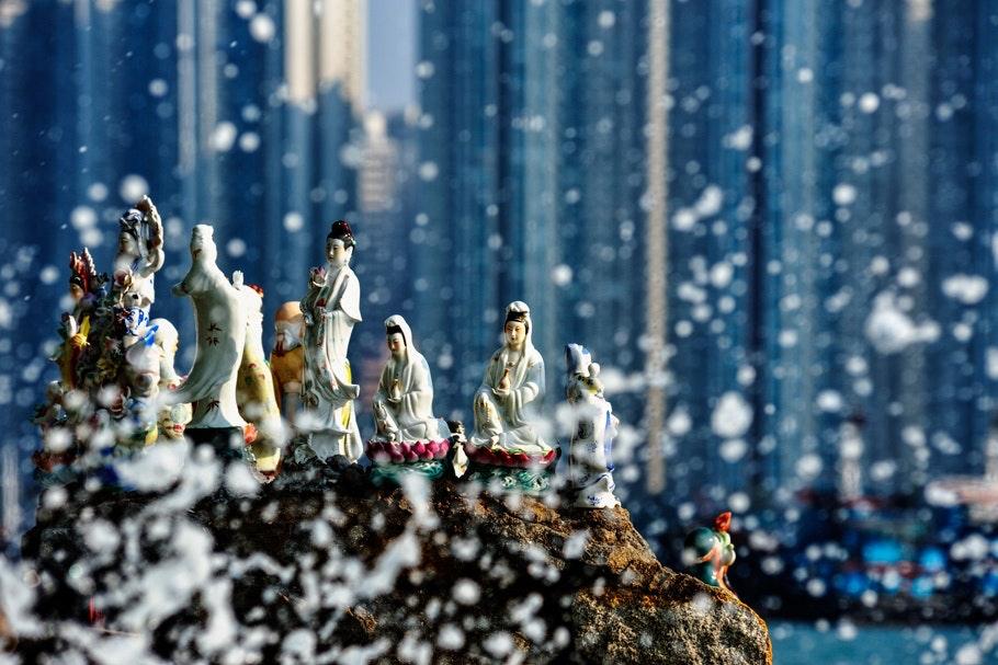 Miniature statues arranged on a wave-sprayed rock