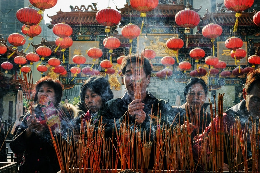 People burning incense and praying at a temple