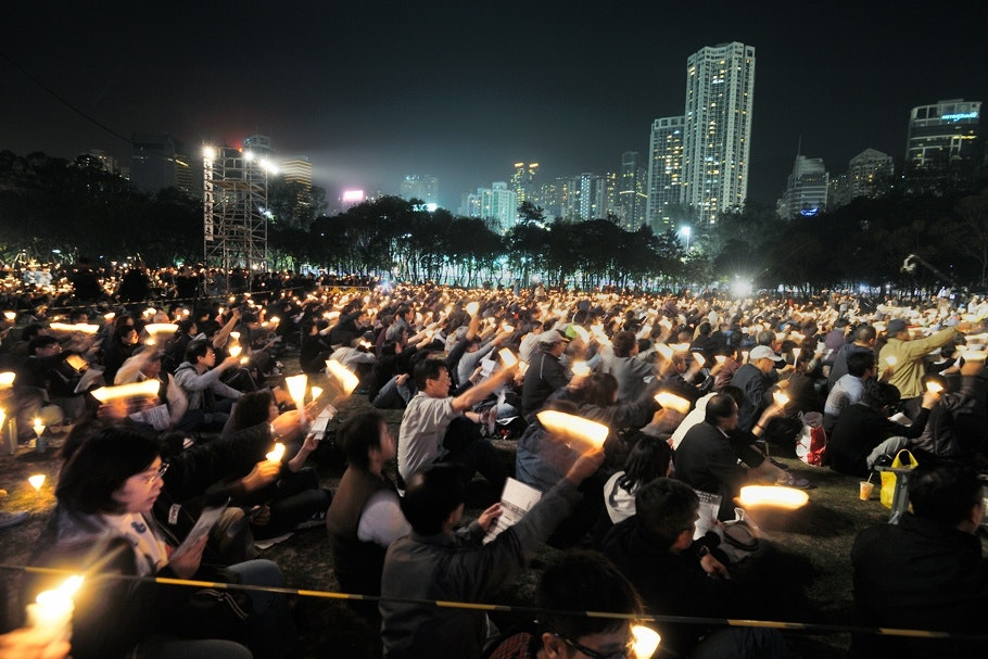 Large crowd seated at a nighttime demonstration