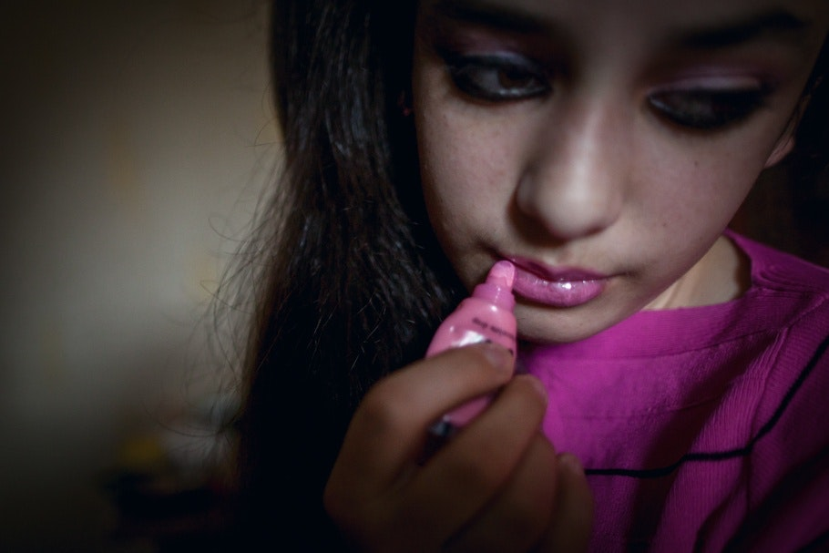 A young girl puts on lip-gloss