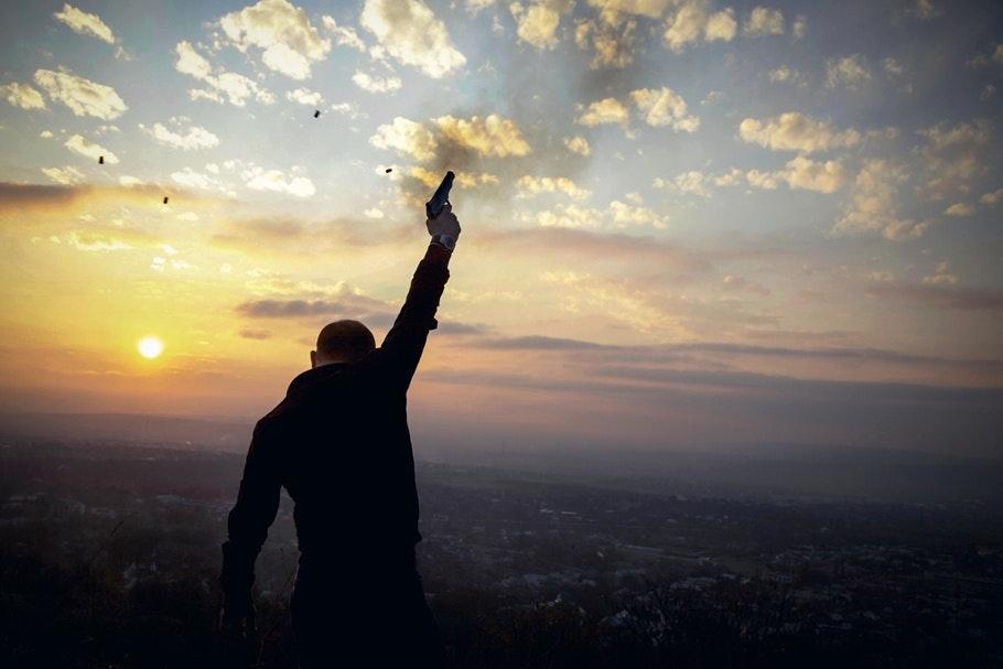 A man shooting a gun in the air