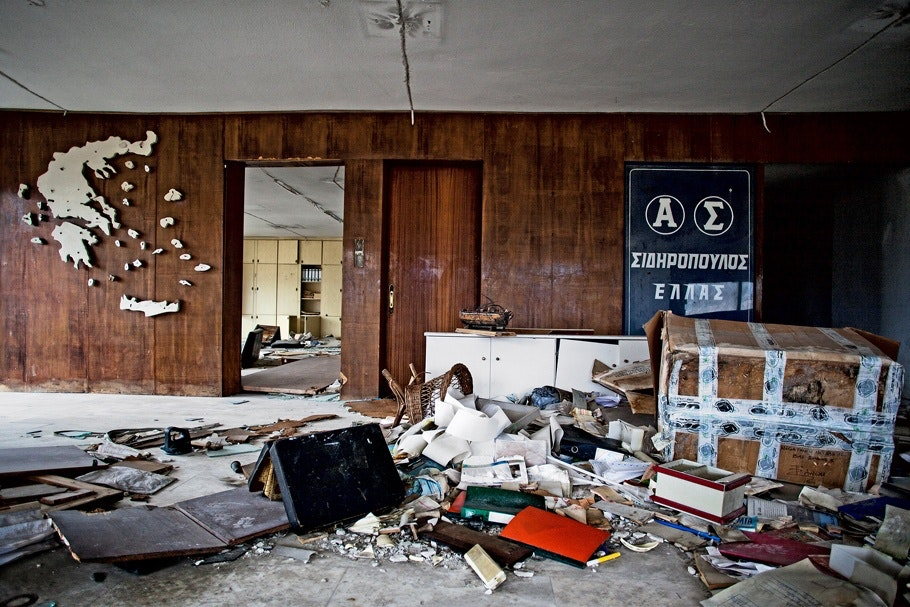 Interior of abandoned office, with Greek map on wall.