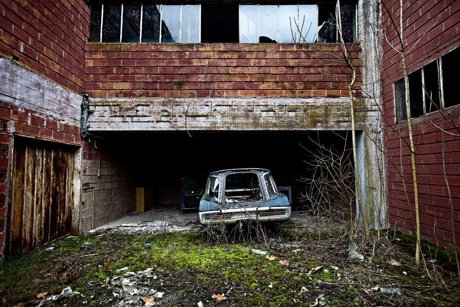 Abandoned car parked outside an abandoned factory building.
