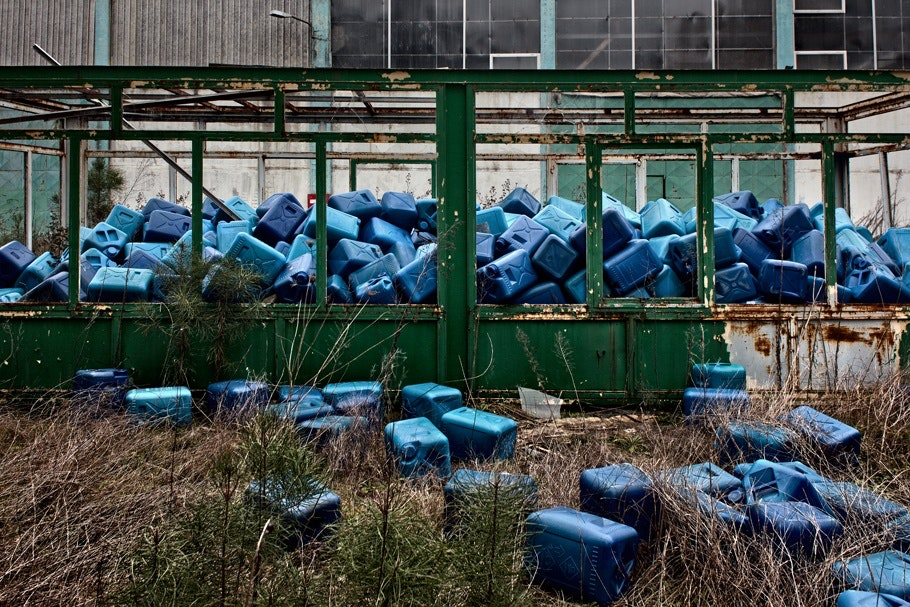 Blue plastic containers piled outside an abandoned factory.
