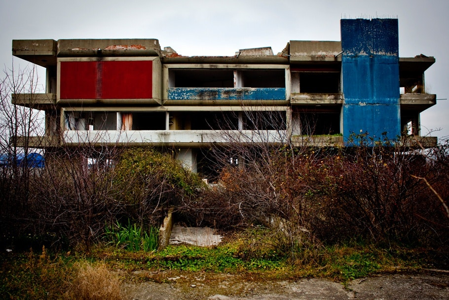 Abandoned factory with red and blue external wall panels.