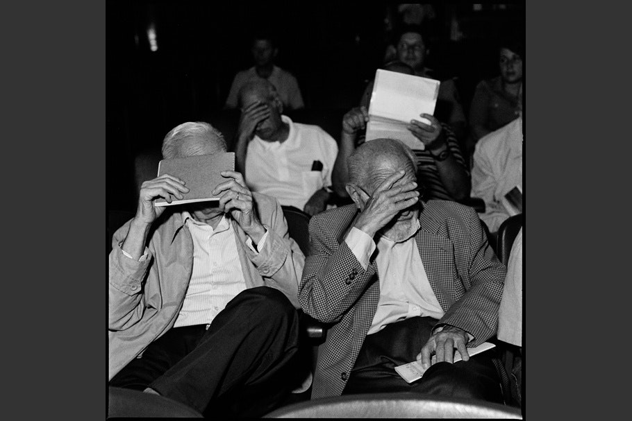 Seated men hiding their faces