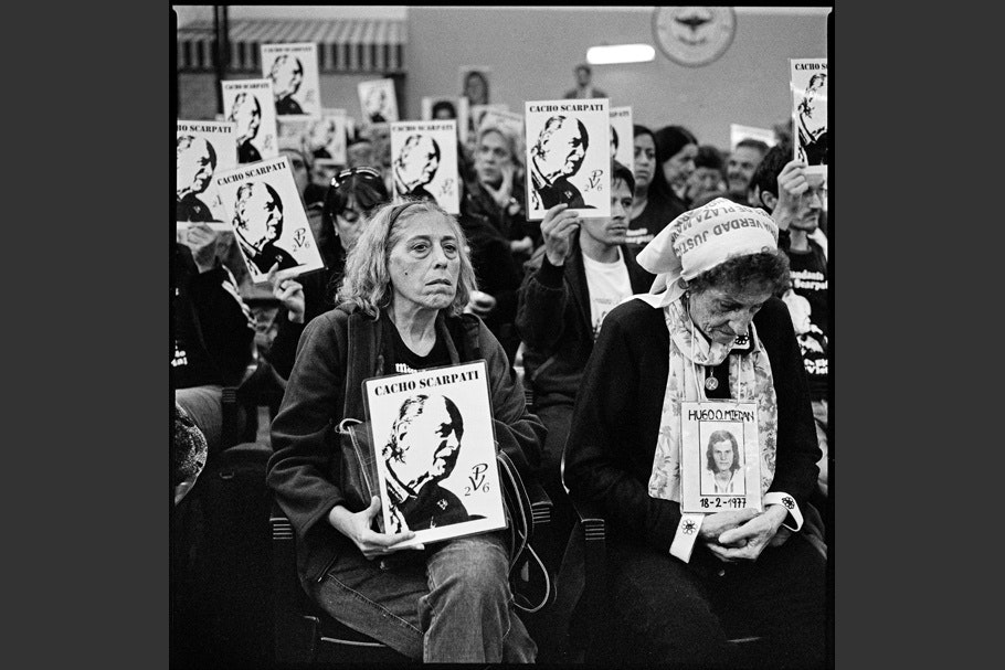 """Courtroom with families and friends of concentration camp victims holding signs that read """"Cacho Scarpati."""""""