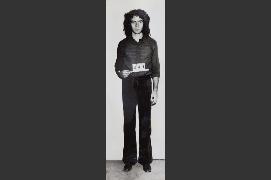 """Mug shot of a man standing and holding sign that reads """"244."""""""