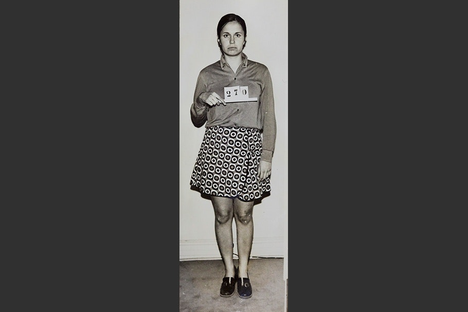 "Mug shot of a woman standing and holding sign that reads ""270."""