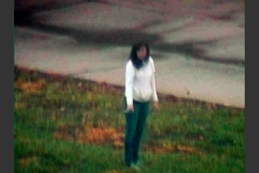 Woman wearing jeans and white shirt standing in grass