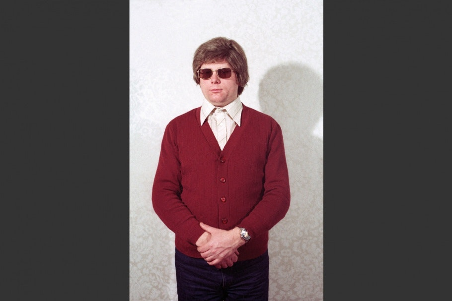 Man with maroon cardigan and sunglasses, hands held in front