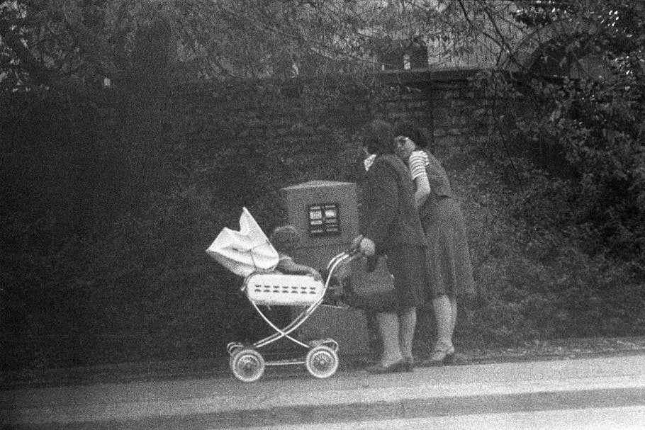 Two women, one pushing baby carriage, in front of mailbox