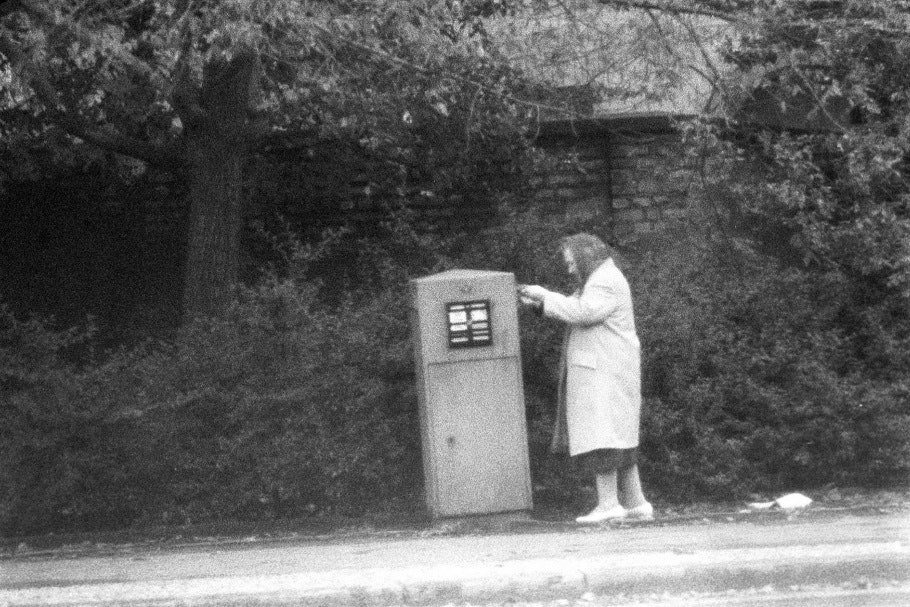 Elderly woman with scarf covering head, placing mail in mailbox