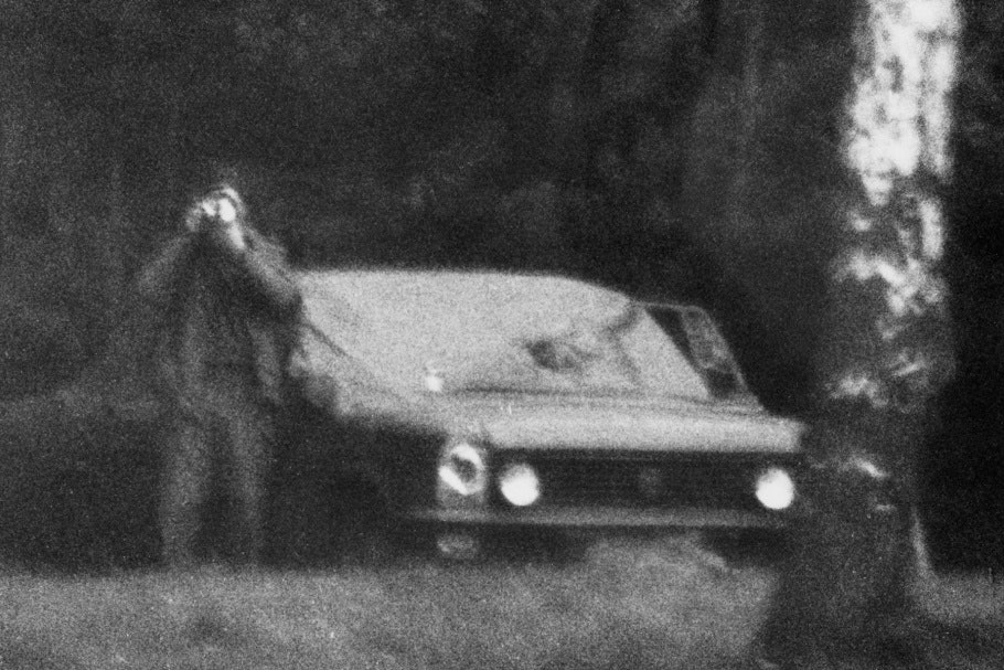 Man standing to the left of a parked car holding camera to his face