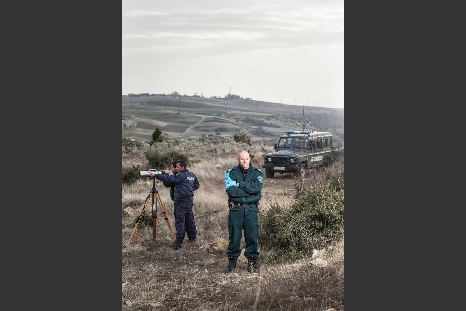 Two border patrol police stand in an open landscape with a jeep in the background