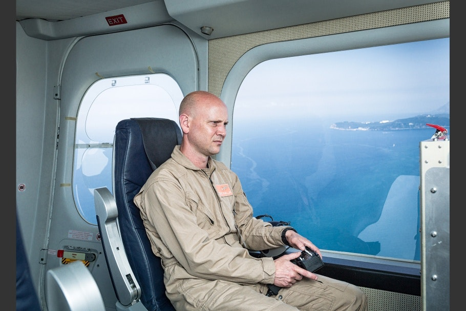 Surveillance camera operator seated inside a zeppelin, with ocean in background