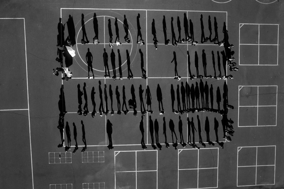 Aerial photograph of schoolyard with shadows of students lined up in four rows
