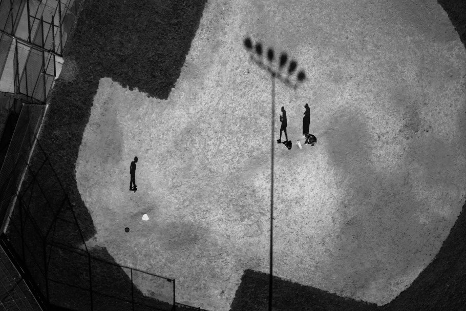 Aerial photograph of three figures and stadium lights casting shadows across a baseball field.