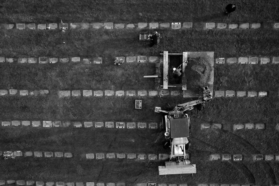 Aerial photograph of rows of headstones and open grave