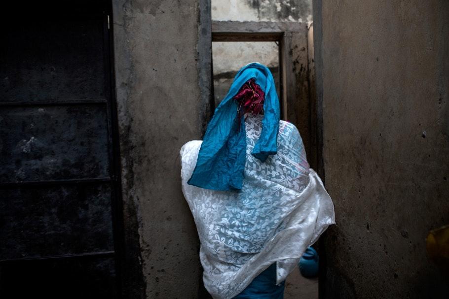 A young woman wearing blue walks through a door