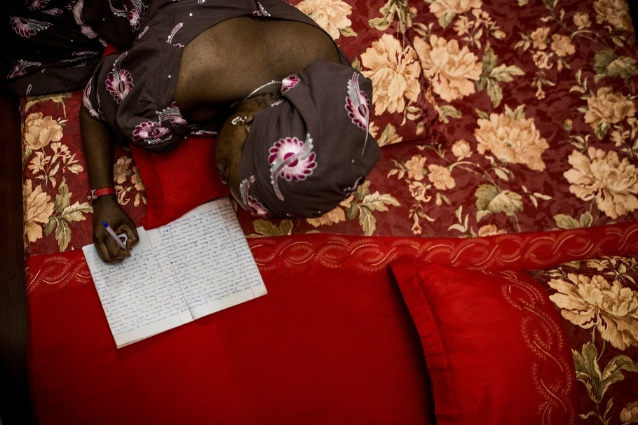 A Nigerian romance novelist writes while lying on a red bed