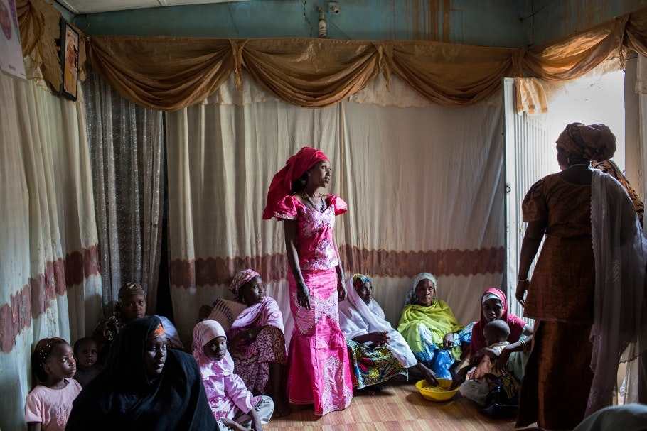 A woman wearing pink stands in the middle of a room during her wedding