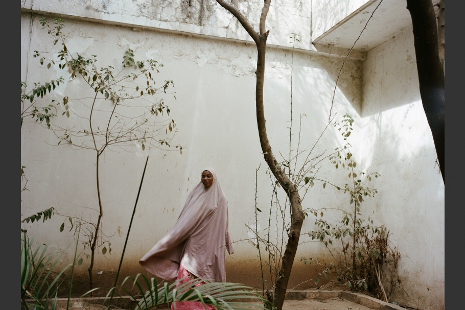 A Nigerian romance novelist wearing pink walks in a courtyard