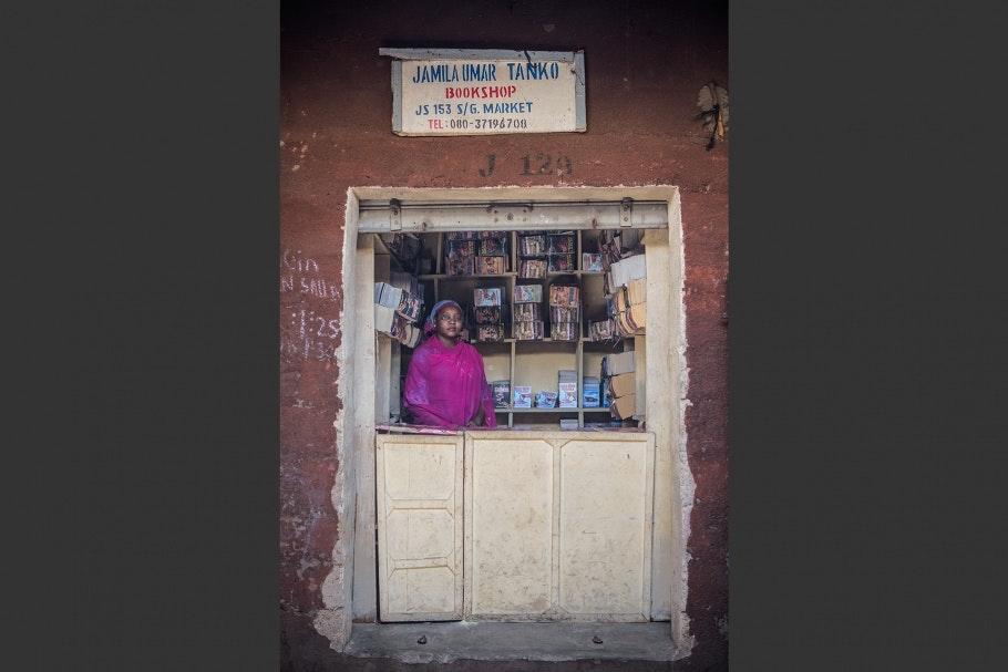 A Nigerian romance novelist stands inside her bookstall