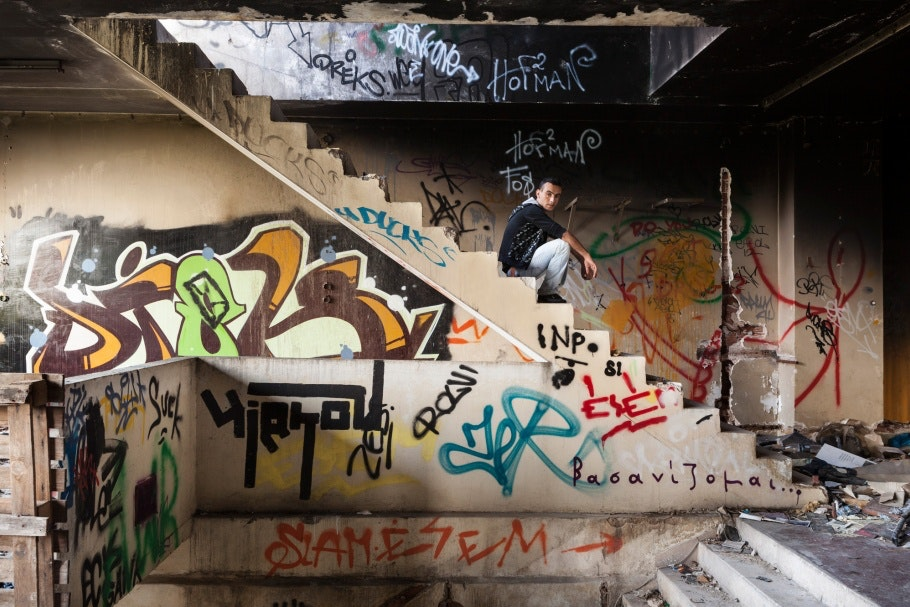 A man sits on the stairs of a deserted building