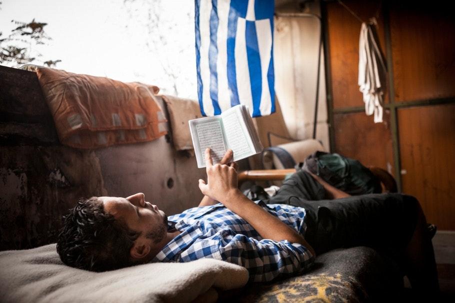 A man reads the Koran beneath a Greek flag